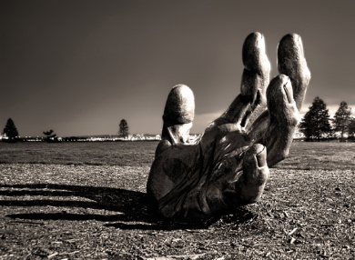 Shows a gigantic hand rising from a barren desert landscape as from one who is drowning…